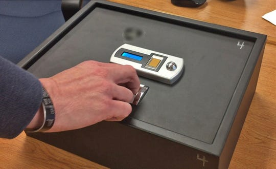 A Jay County school official demonstrates how their gun case works.