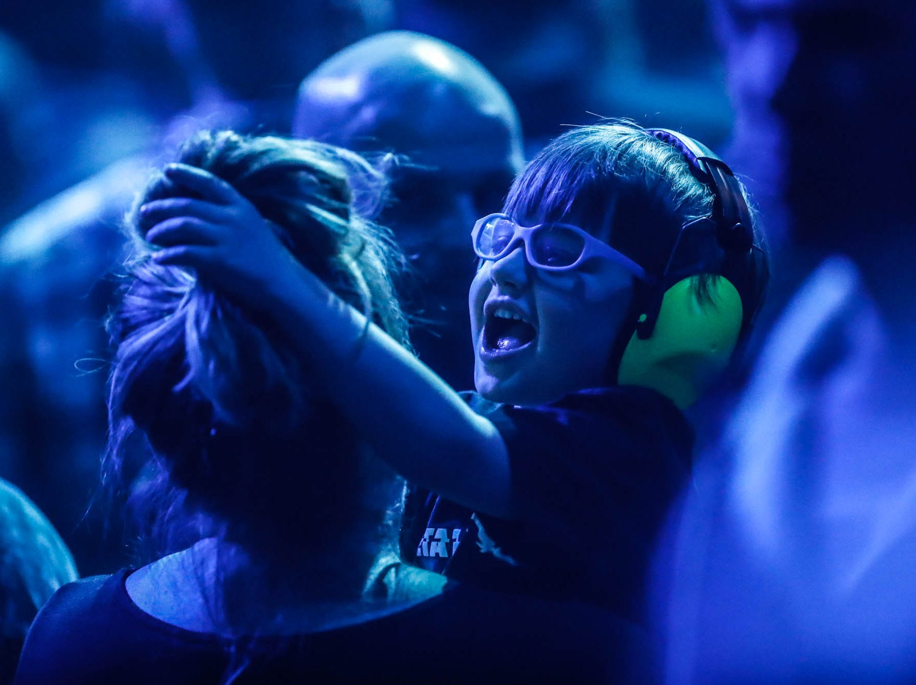 A young fans helps adjust a caregivers hair while waiting for Metallica to take the stage at Bankers Life Fieldhouse on Monday, March 11, 2019.