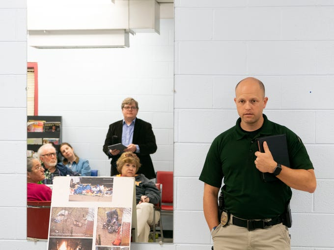 Knoxville Police Department officer Thomas Clinton answers questions during the Vestal Community Organization's monthly meeting at the South Knoxville Community Center on Monday, March 11, 2019. Clinton, who does homeless outreach on behalf of the department, addressed South Knoxville residents' concerns regarding the homeless. At left, reflected on the mirror is Michael Dunthorn, Knoxville's homeless program coordinator.