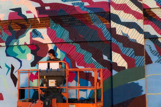 Seattle-based artist Addison Karl works on a mural. City officials selected him to complete a Market Square Garage mural, which they hope he will start in the fall.