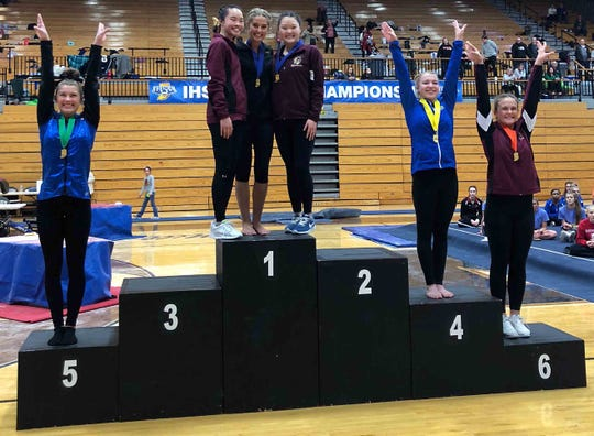 McCutcheon senior Crysta Dilley, center, stands atop the podium with Chesterton's Mia Park and Sophia Hunzelman after the trio tied for the state championship on bars at last Saturday's IHSAA state finals.