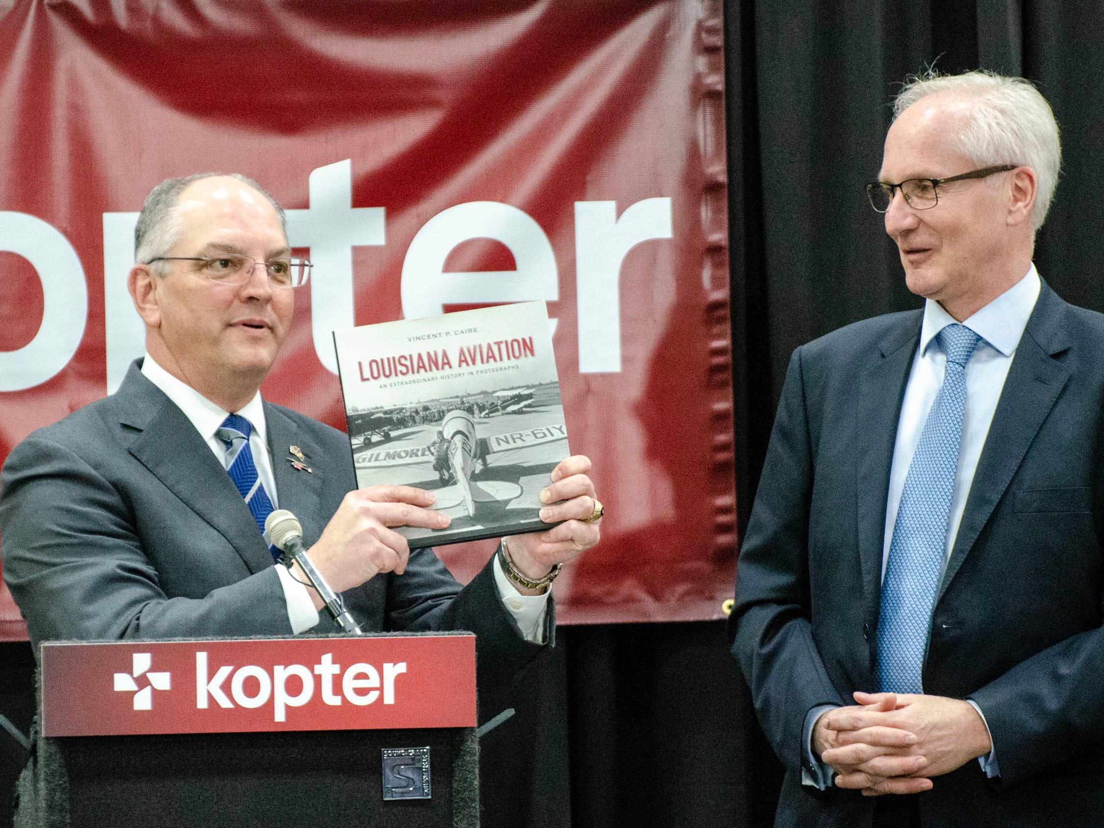 Governor John Bel Edwards presents book to CEO Andreas Lowenstein at the Kopter Manufacturing Faciltiy Dedication.
