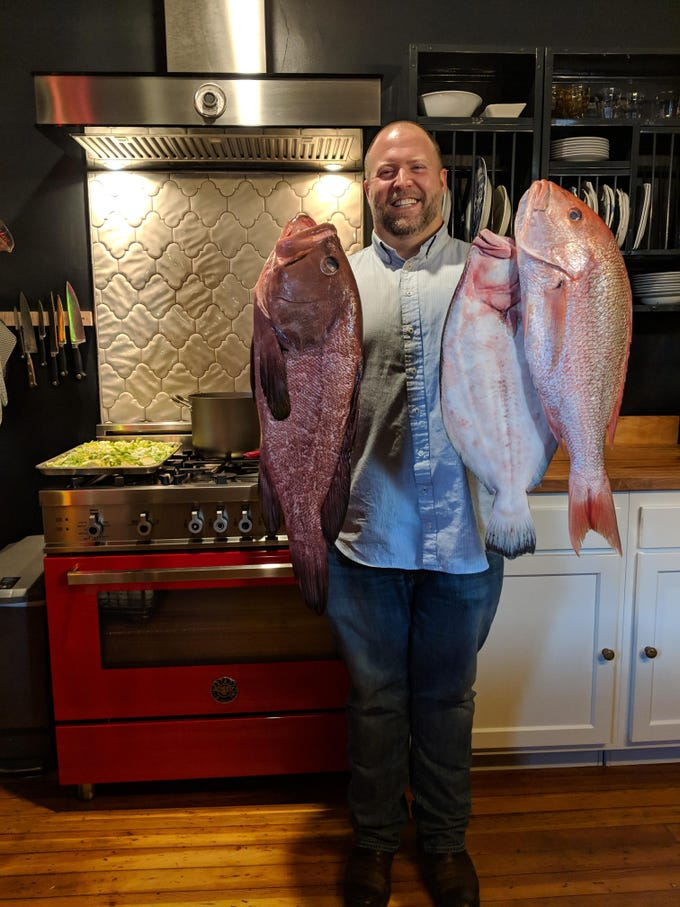 It's no 300 pound alligator but Volare chef Josh Moore obliged with his famous catch of the day photo in food writer Dana McMahan's kitchen. From left to right, Moore is holding a red grouper, fluke and red snapper.