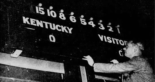 UK athletics director Bernie Shively looks over the new electronic scoreboard installed at the Jefferson County Armory before the 1941 SEC Tournament.