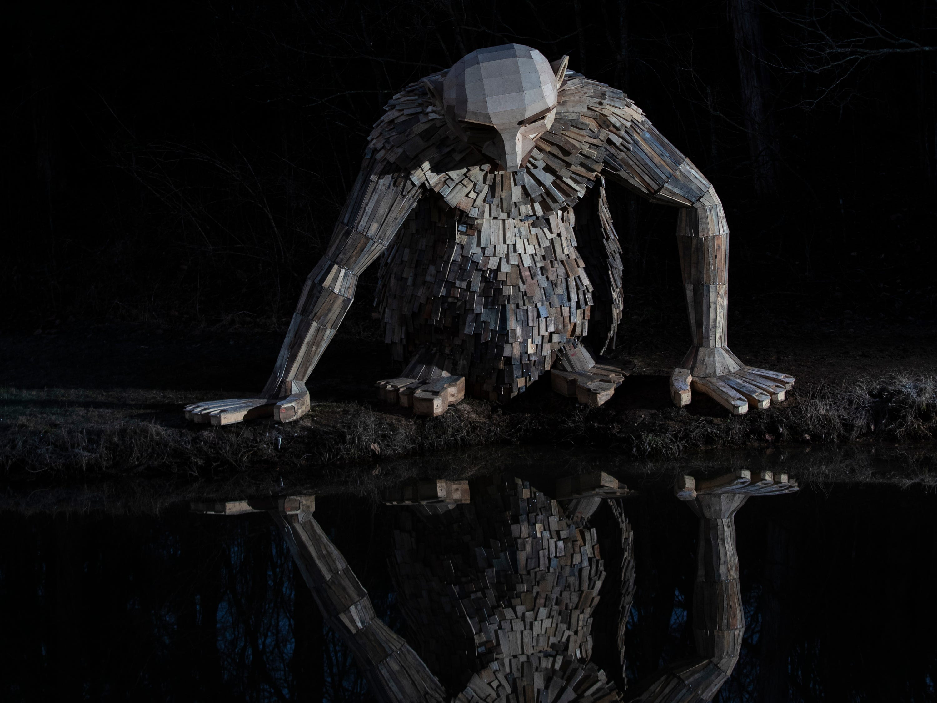 """""""Little Nis,"""" gazes into the waters of Holly Pond at Bernheim Forest. His is one of three giant trolls created by sculptor Thomas Dambo. Feb. 27, 2019"""
