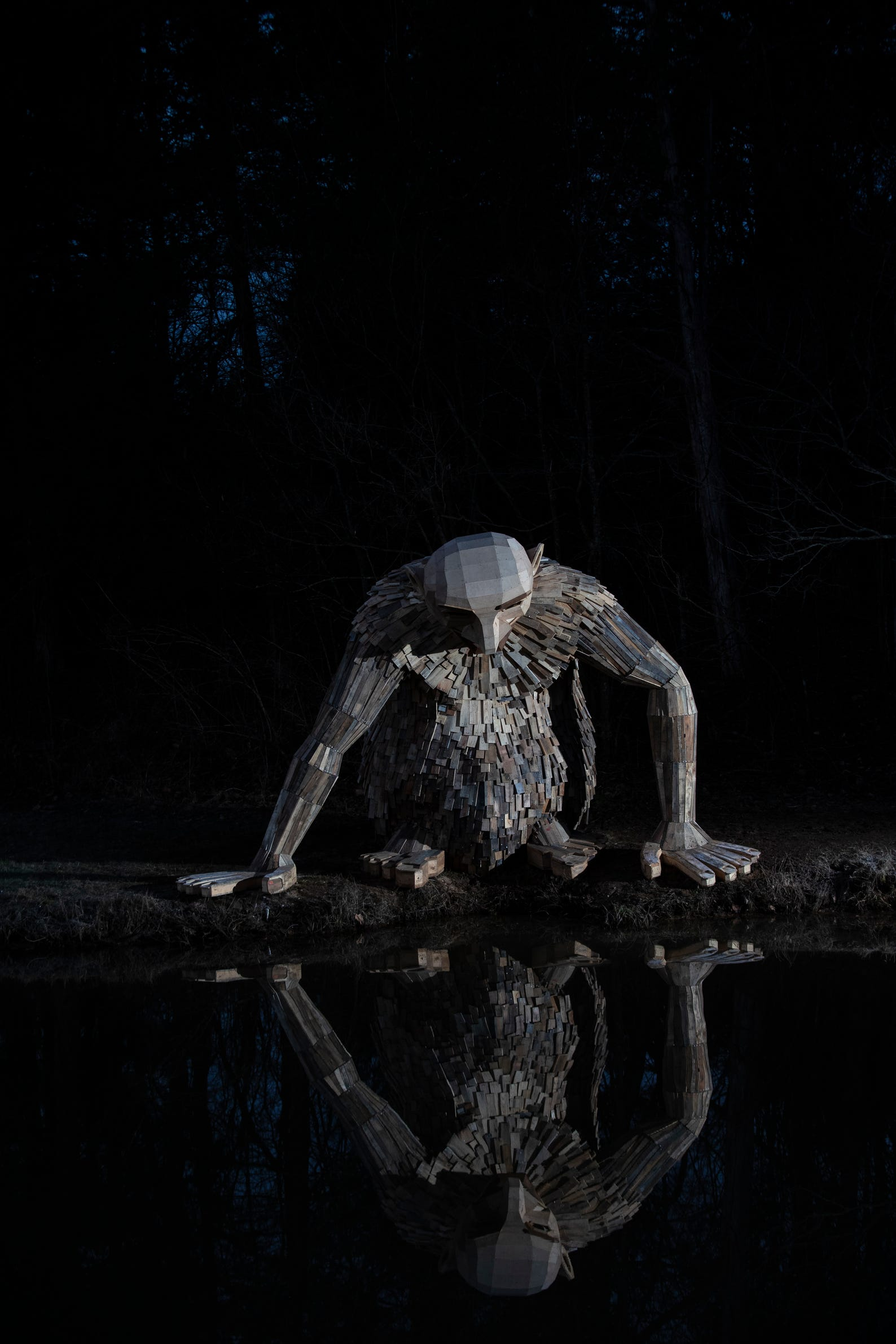"""Little Nis,"" gazes into the waters of Holly Pond at Bernheim Forest. His is one of three giant trolls created by sculptor Thomas Dambo. Feb. 27, 2019"