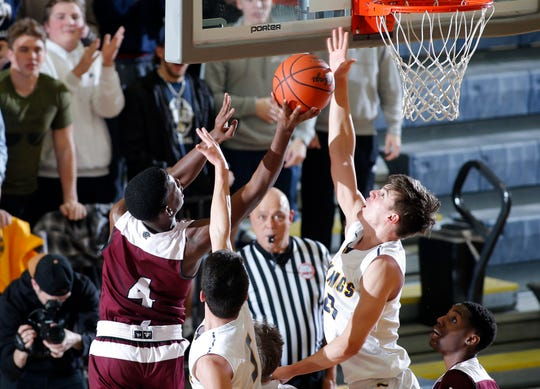 Haslett's Sam Laczynski, right, blocks a shot by River Rouge's Legend Geeter (4), Tuesday, March 12, 2019, in Chelsea, Mich.