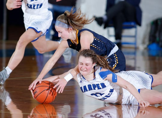 Haslett's Emma Campbell, top, and Battle Creek Harper Creek's Abbey Hicks dive for the ball, Monday, March 11, 2019, in Ionia, Mich.