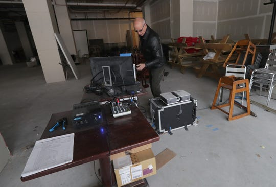 """Dick Blau adjusts the projector and equipment he uses in a vacant storefront on West Wisconsin Avenue for his """"The 730 Projection"""" photo show."""