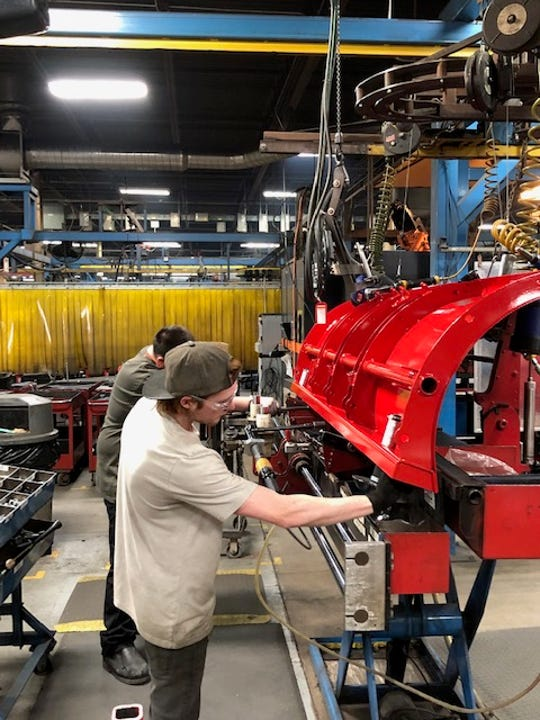 Douglas Dynamics Inc. employees work on a snowplow blade at the company's Milwaukee plant.