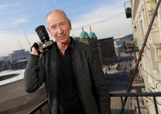Dick Blau stands on the balcony of his eighth floor Milwaukee condo. From the balcony, he can see the County Courthouse, Milwaukee County Historical Society, Fiserv Forum and other downtown buildings.