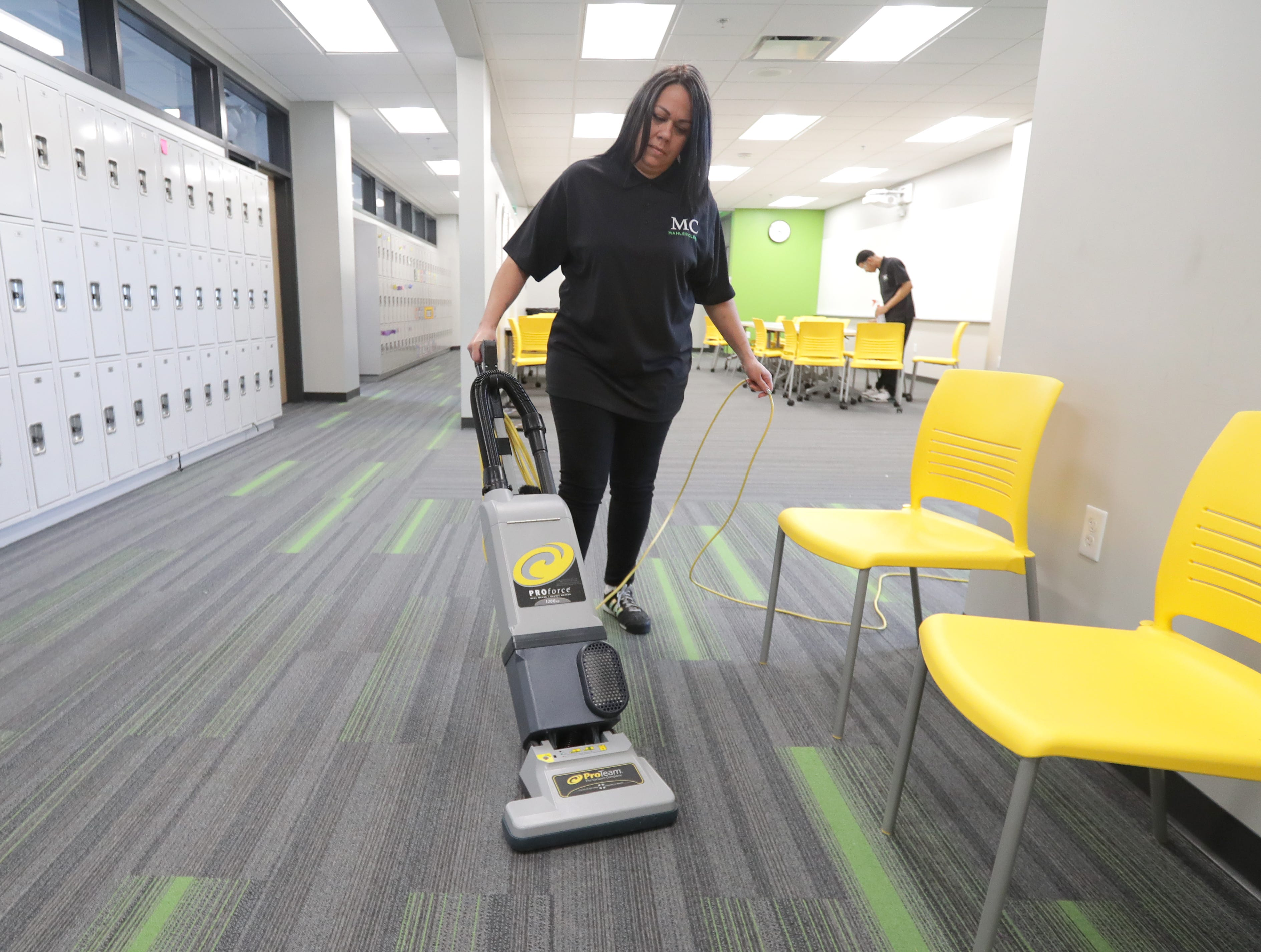MahlerClean service representative Priscilla Castro vacuums as fellow service representative Tercellus Carr wipes down tables March 11 at St. Augustine Academy in Milwaukee.