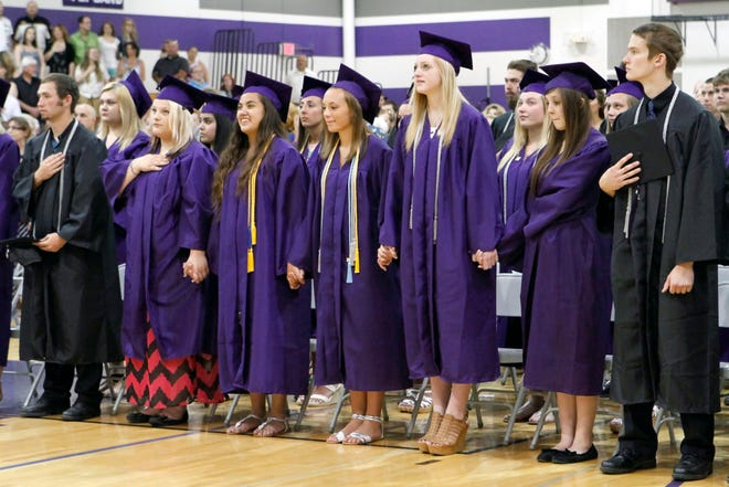 Palmyra-Eagle High School graduates stand for the national anthem during the graduation ceremony June 1, 2014. The Palmyra-Eagle Area School District is holding an $11.5 million referendum April 2. District officials say the extra money is needed to keep the district from dissolving.