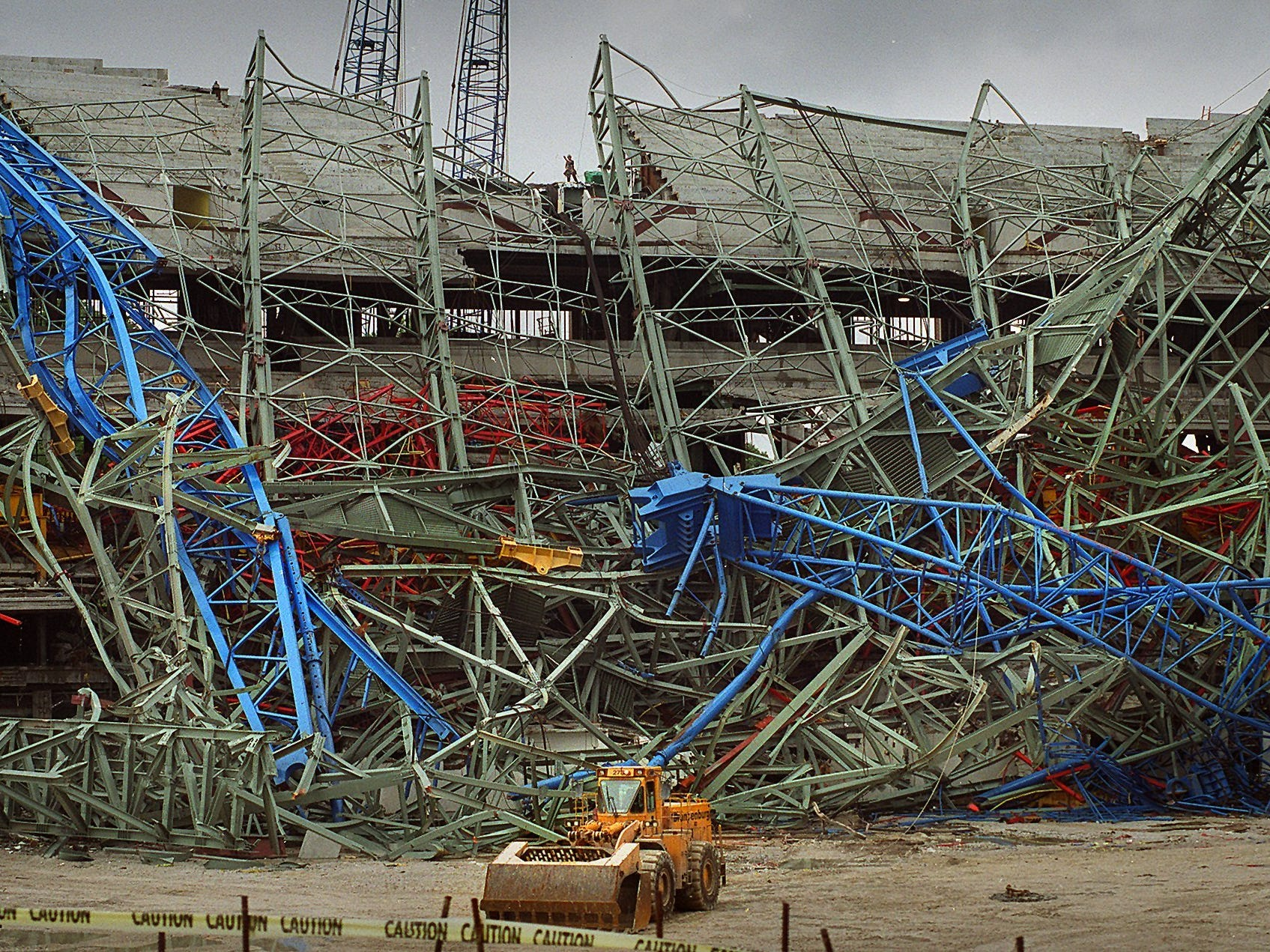 "The twisted wreckage of the giant crane known as ""Big Blue"" and the roof section it was lifting are still jumbled at Miller Park, but stadium officials claim they are pleased with the progress that is being made. August 19, 1999."