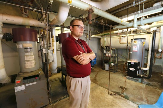 Jonathan Mitchell, director of finance and operations for the St. Francis School District, looks over parts of an aging boiler system at Deer Creek Intermediate School in July 2017. If an April 2 referendum is approved, Deer Creek would be closed and Willow Glen Primary School would be renovated to accommodate the district's 4-year-old kindergarten through eighth-grade students at a single school.