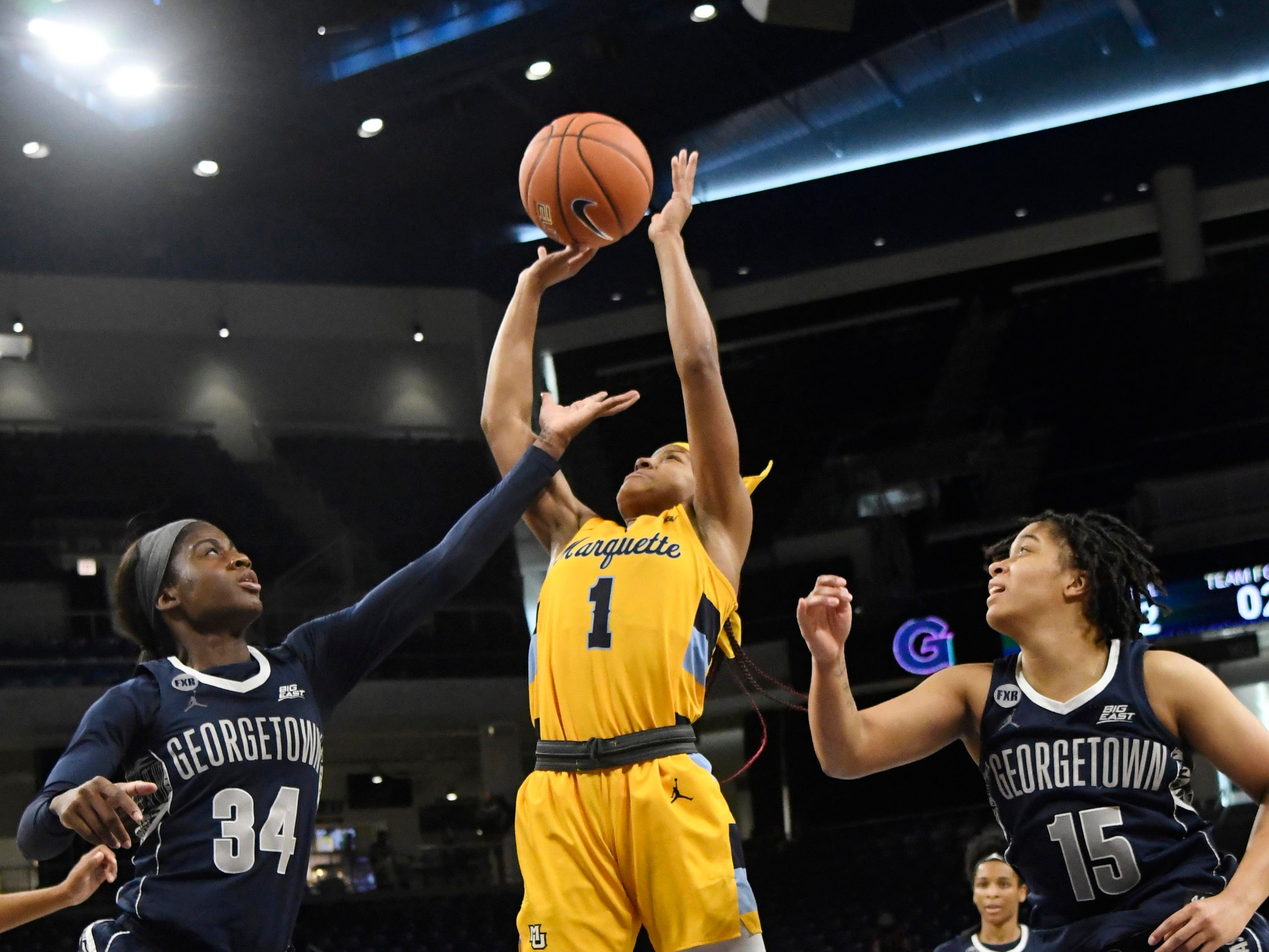 Marquette guard Danielle King splts Georgetown defenders  Dorothy Adomako and  Mikayla Venson.