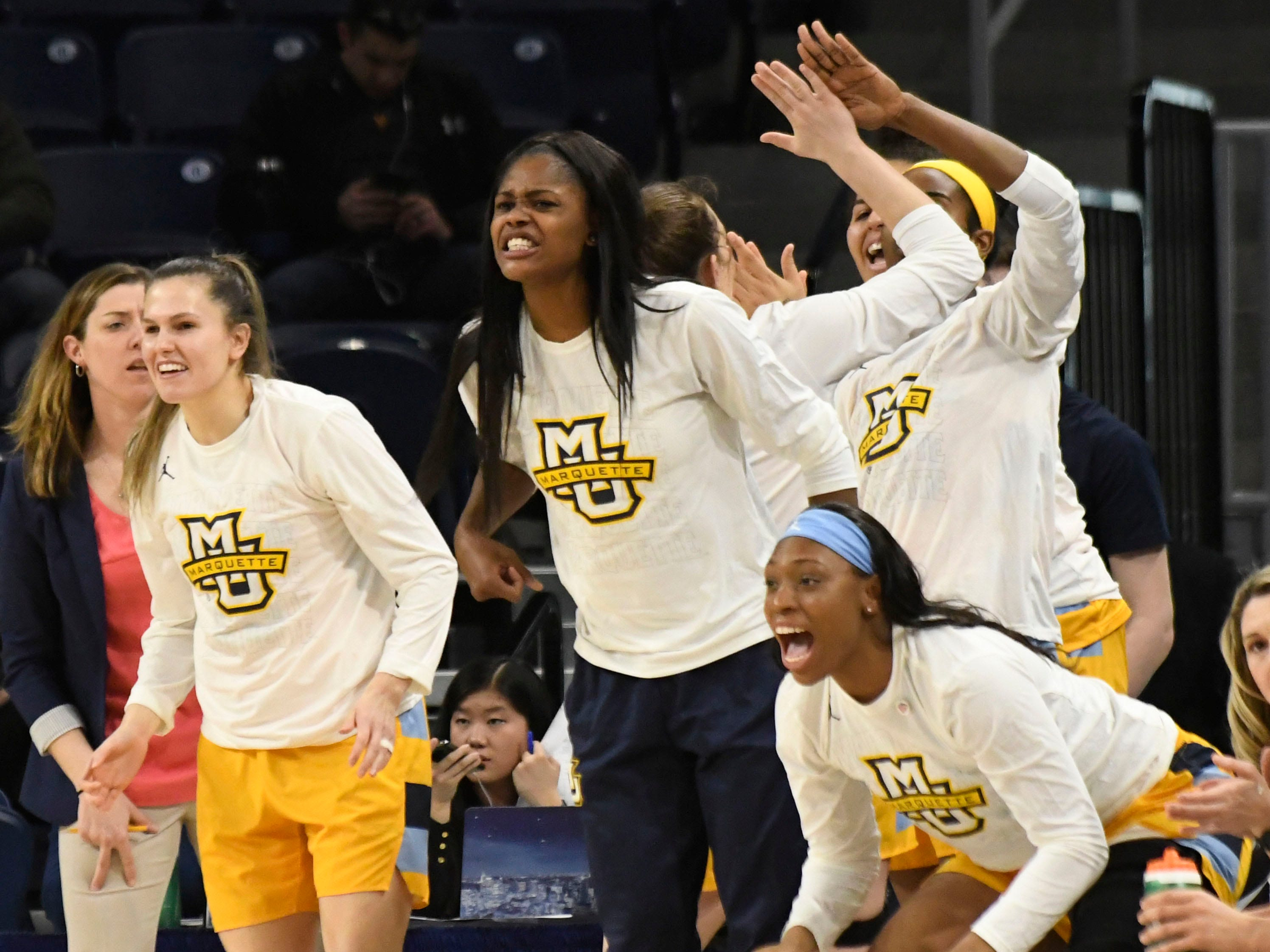 The Marquette bench celebrates a three-point basket in the first half at the Big East tournament in Chicago.