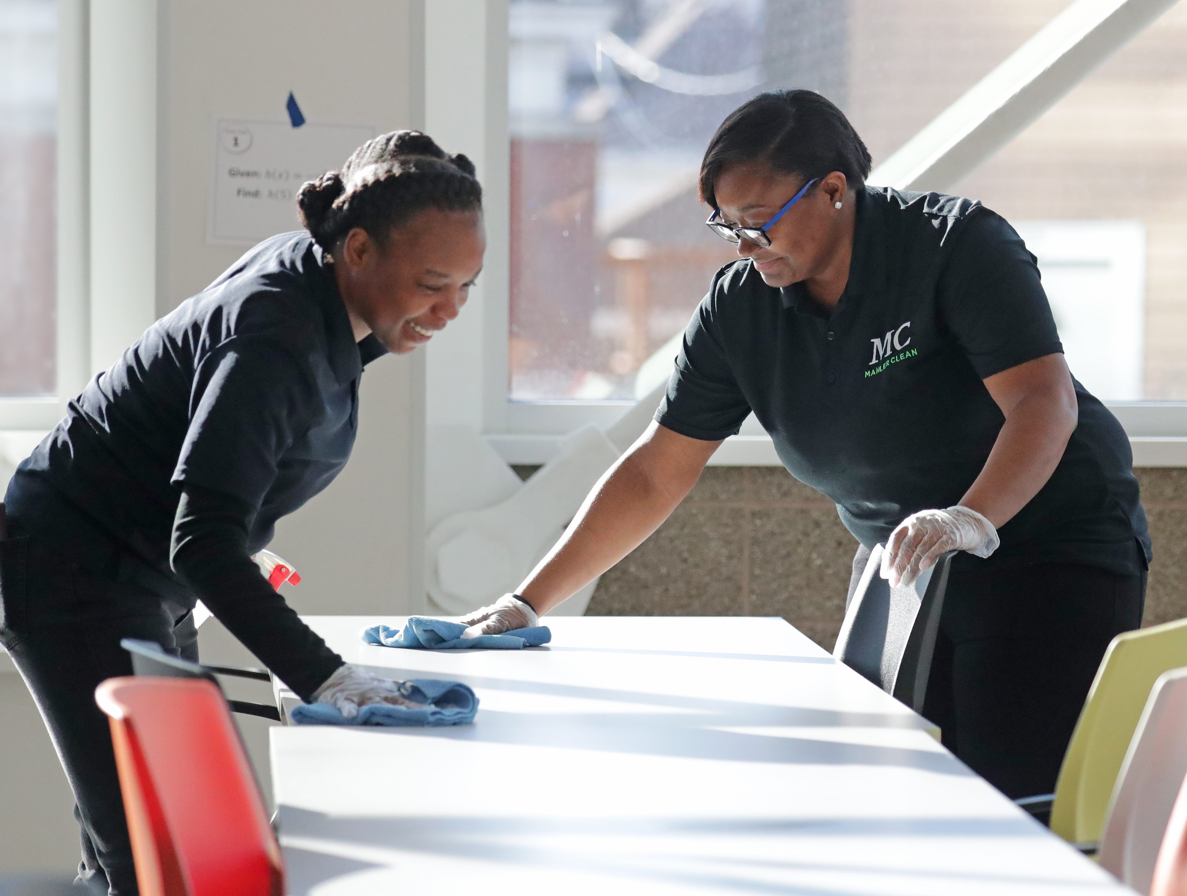 MahlerClean manager Kareen Anthony (left) and lead representative Denise Watkins wipe down tables in the lunchroom at St. Augustine Academy on South Fifth Street in Milwaukee on  March 11.