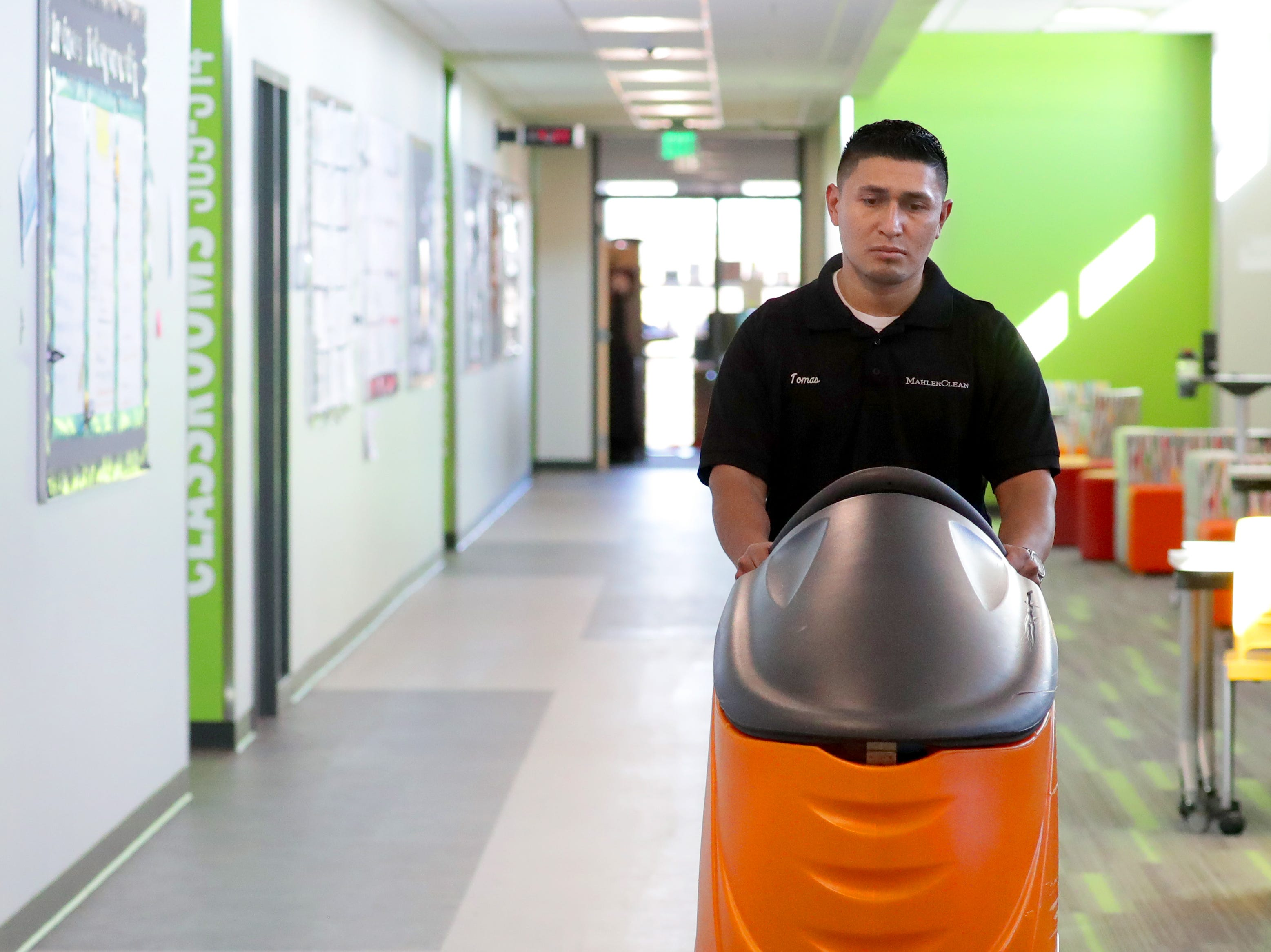 MahlerClean floor crew manager Tomas Perez cleans the floor at St. Augustine Academy on South Fifth Street in Milwaukee.