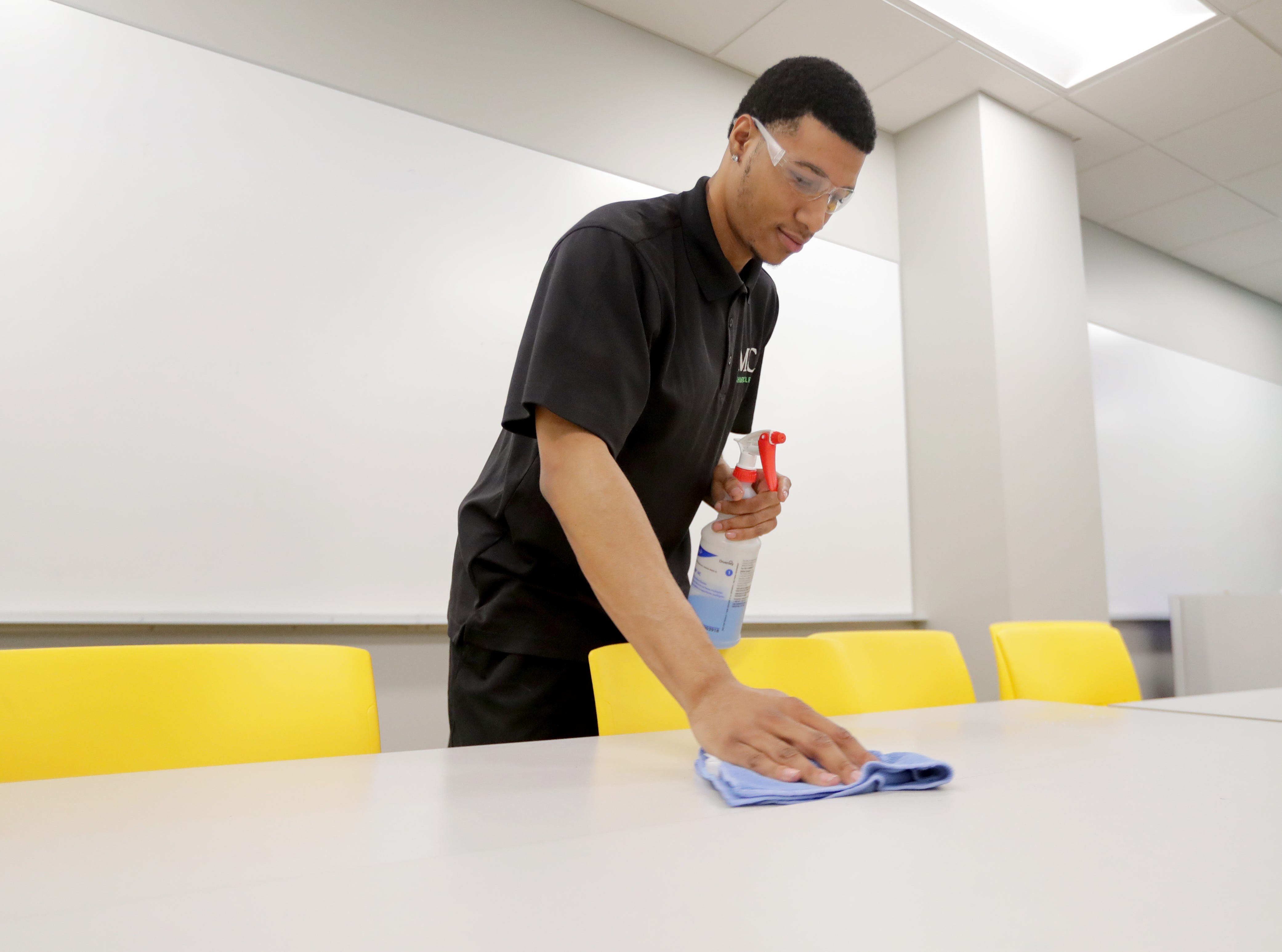 MahlerClean service representative Tercellus Carr wipes down tables after the school day March 11 at St. Augustine Academy on South Fifth Street in Milwaukee.