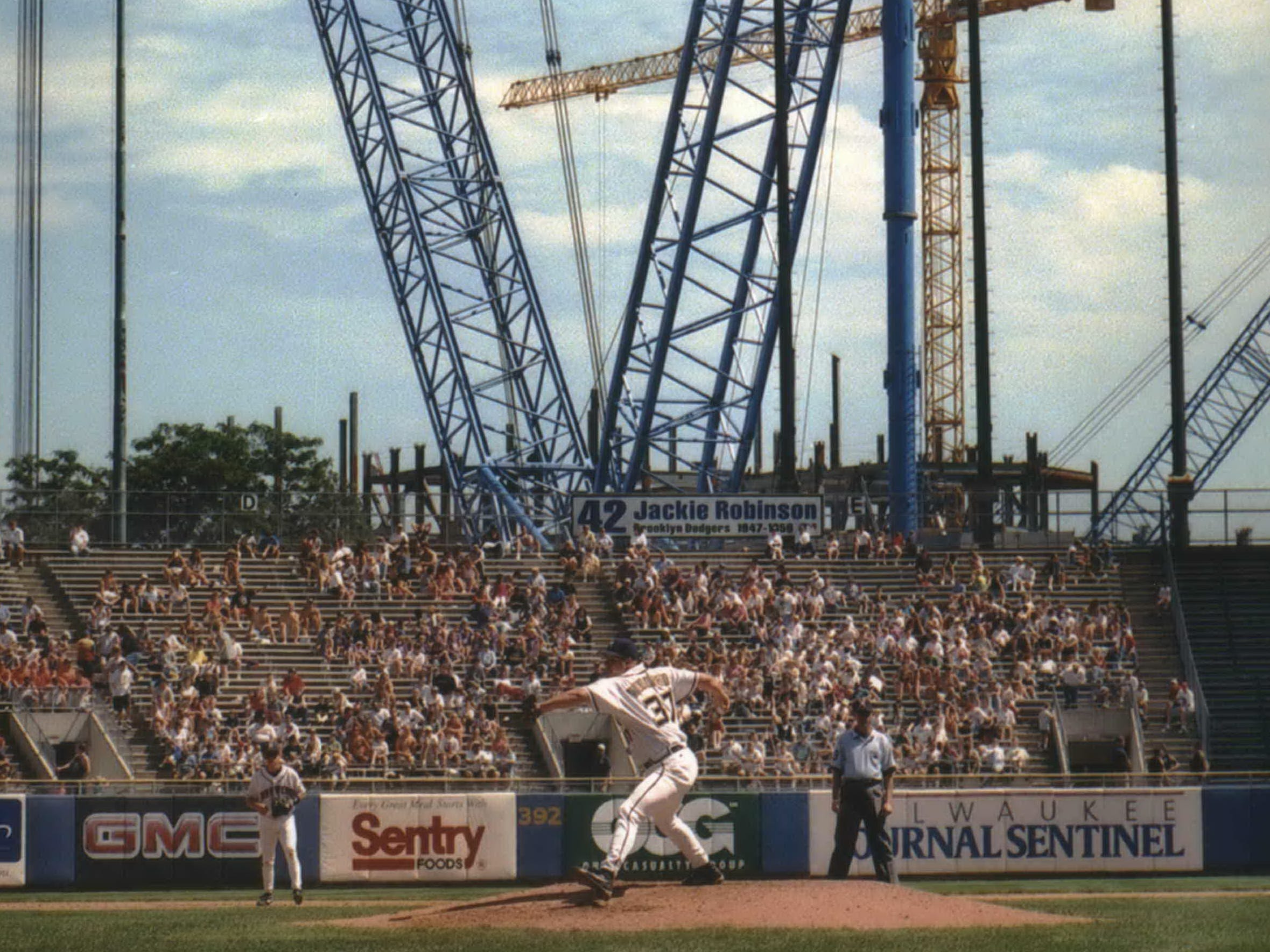 Steve Woodard of the brewers works the mound Wednesday as Big Blue, a 467-foot crane, extends over the bleachers at County Stadium. The crane is used to lift the panels for Miller Park's retractable roof.
