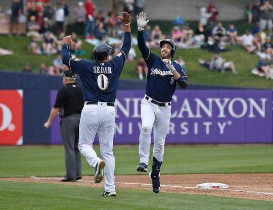 Ryan Braun celebrates his home run with third base coach Ed Sedar in the third inning.