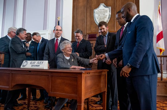 Alabama Governor Kay Ivey hands out pens after she signs the gas tax bill in the state capitol building in Montgomery, Ala., on Tuesday March 12, 2019.