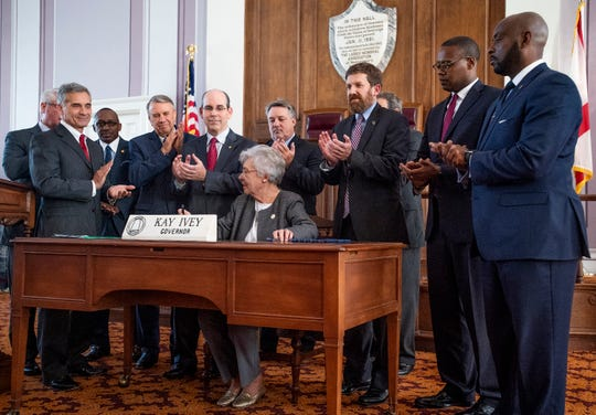 Legislators applaud as Alabama Governor Kay Ivey signs the gas tax bill in the state capitol building in Montgomery, Ala., on Tuesday March 12, 2019.
