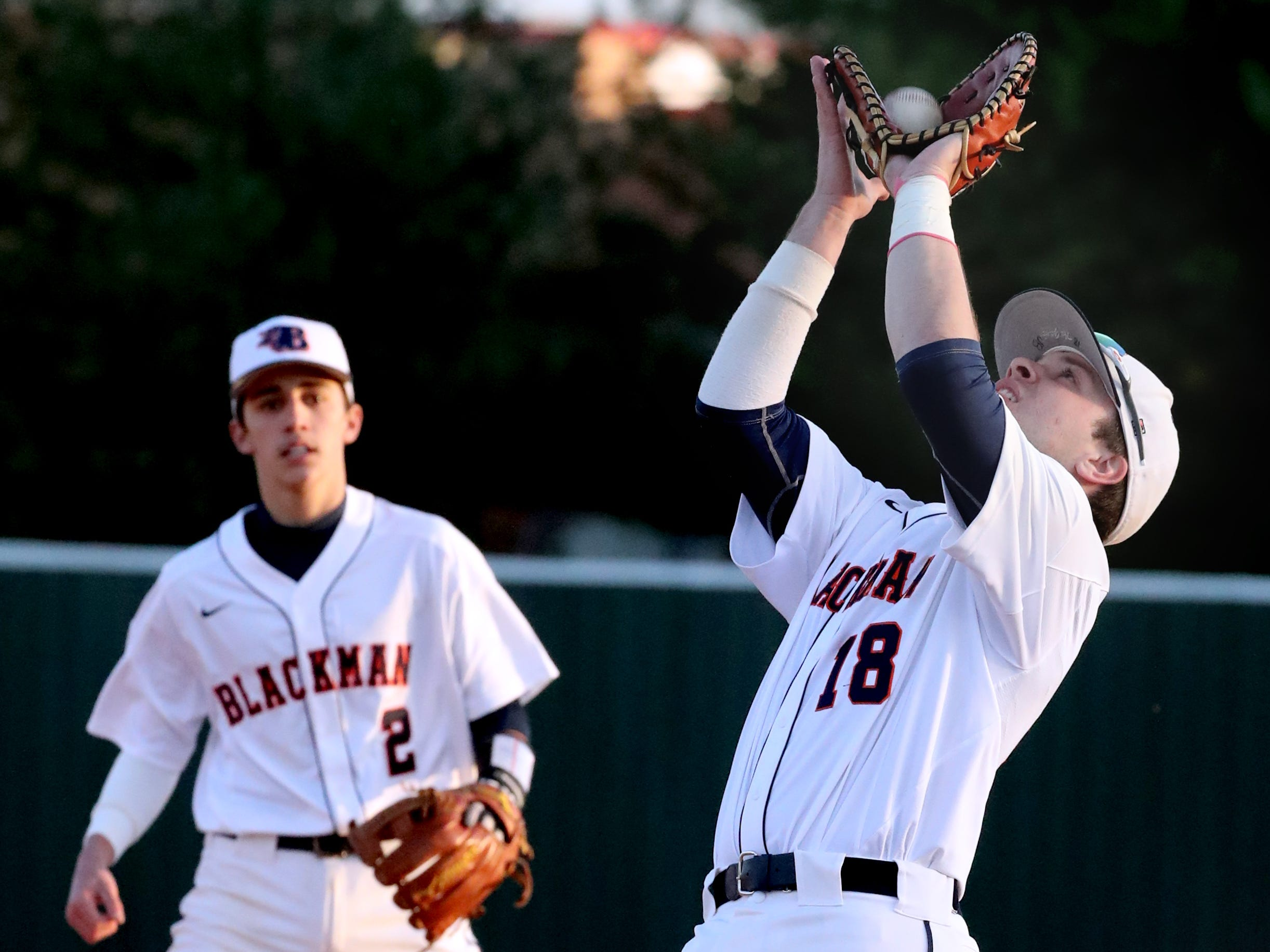Blackman's Jon Blalock (18) makes a catch and an out as Blackman's Carter Warner (2) watches from the background during the game against Siegel, on Monday, March 11, 2019.