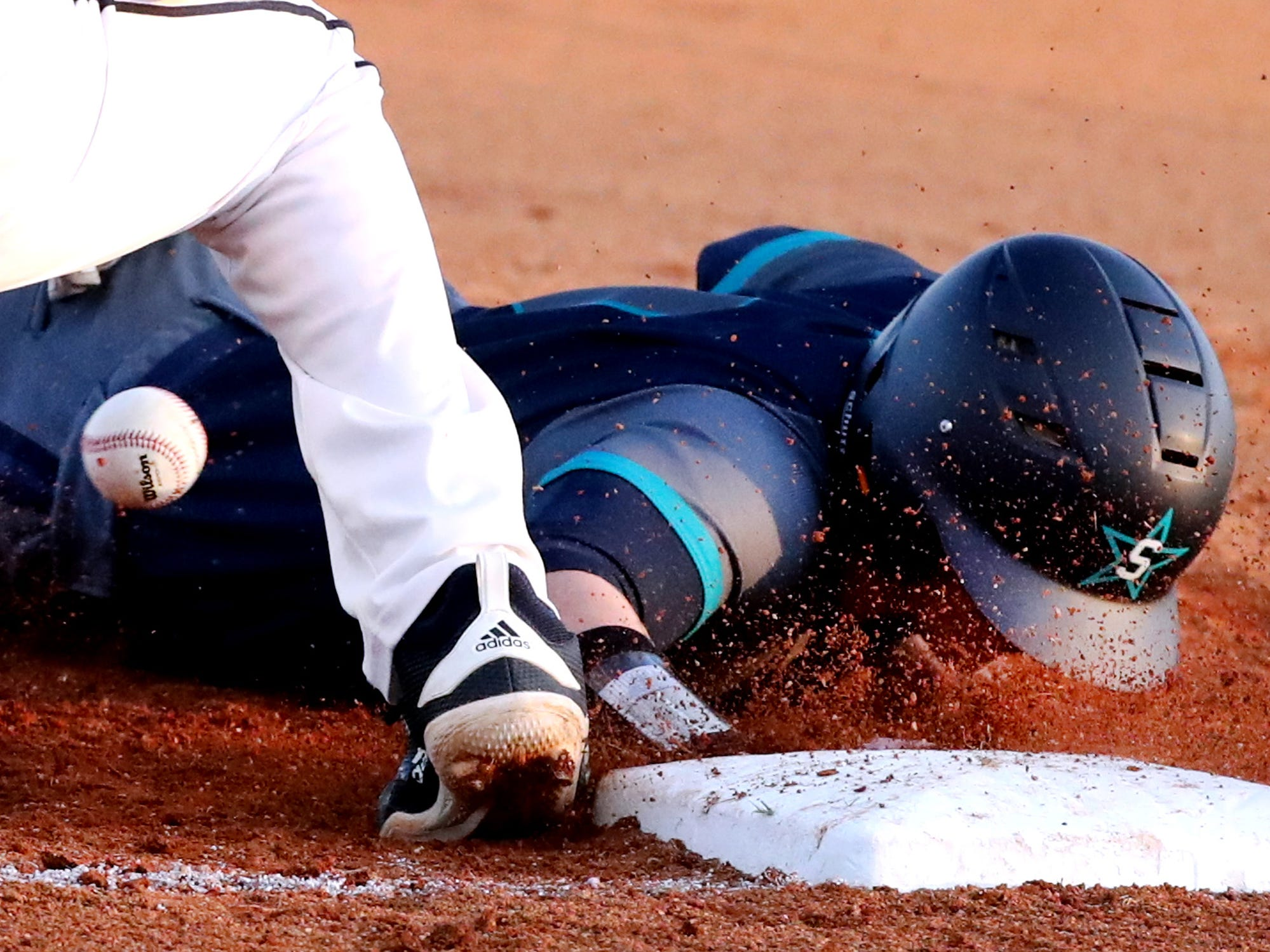 Siegel's Evan Milligan (9) dives back to first base as Blackman's Jon Blalock (18) misses the catch as he tries to tag out Milligan on Monday, March 11, 2019.