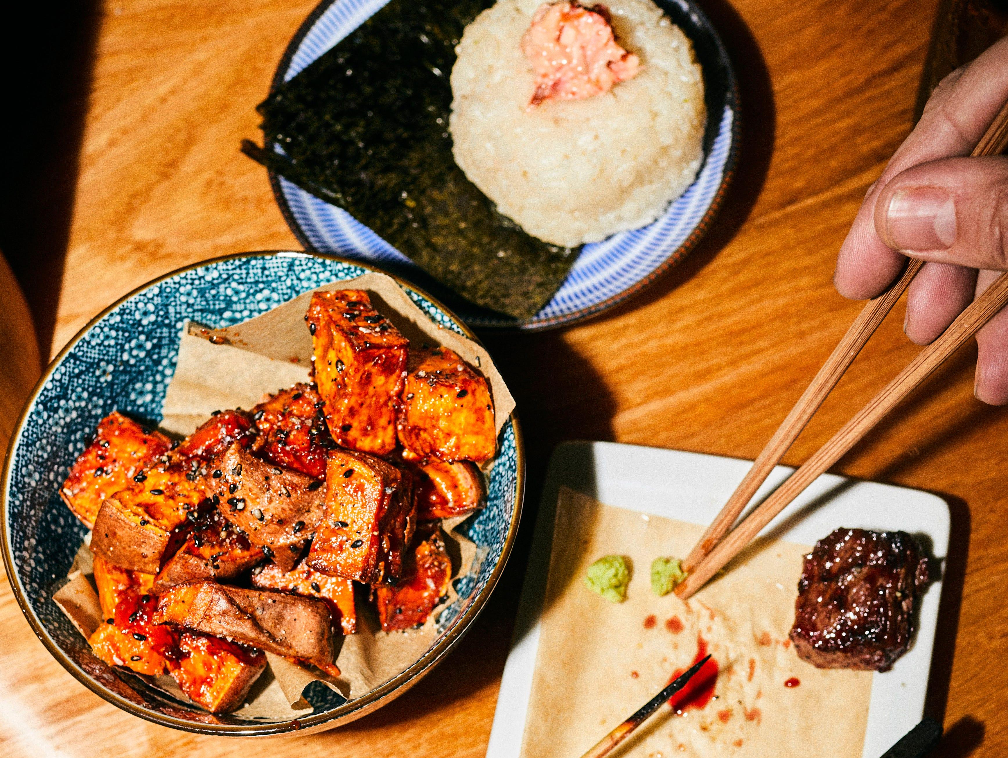 Crispy sweet potatoes in honey-tamari sauce, salmon onigri, skewered steak and chicken at Bar Otaku.