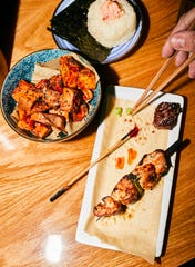 Crispy sweet potatoes in honey-tamari sauce, salmon onigri, skewered steak and chicken at Bar Otaku.