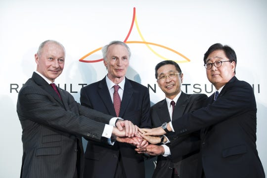 Renault SA CEO Thierry Bollore, left, Chairman Jean-Dominique Senard, Nissan Motor Co. CEO Hiroto Saikawa and Mitsubishi Motors Corp. CEO Osamu Masuko shake hands during a joint news conference March 12, 2019, in Yokohama, Japan.