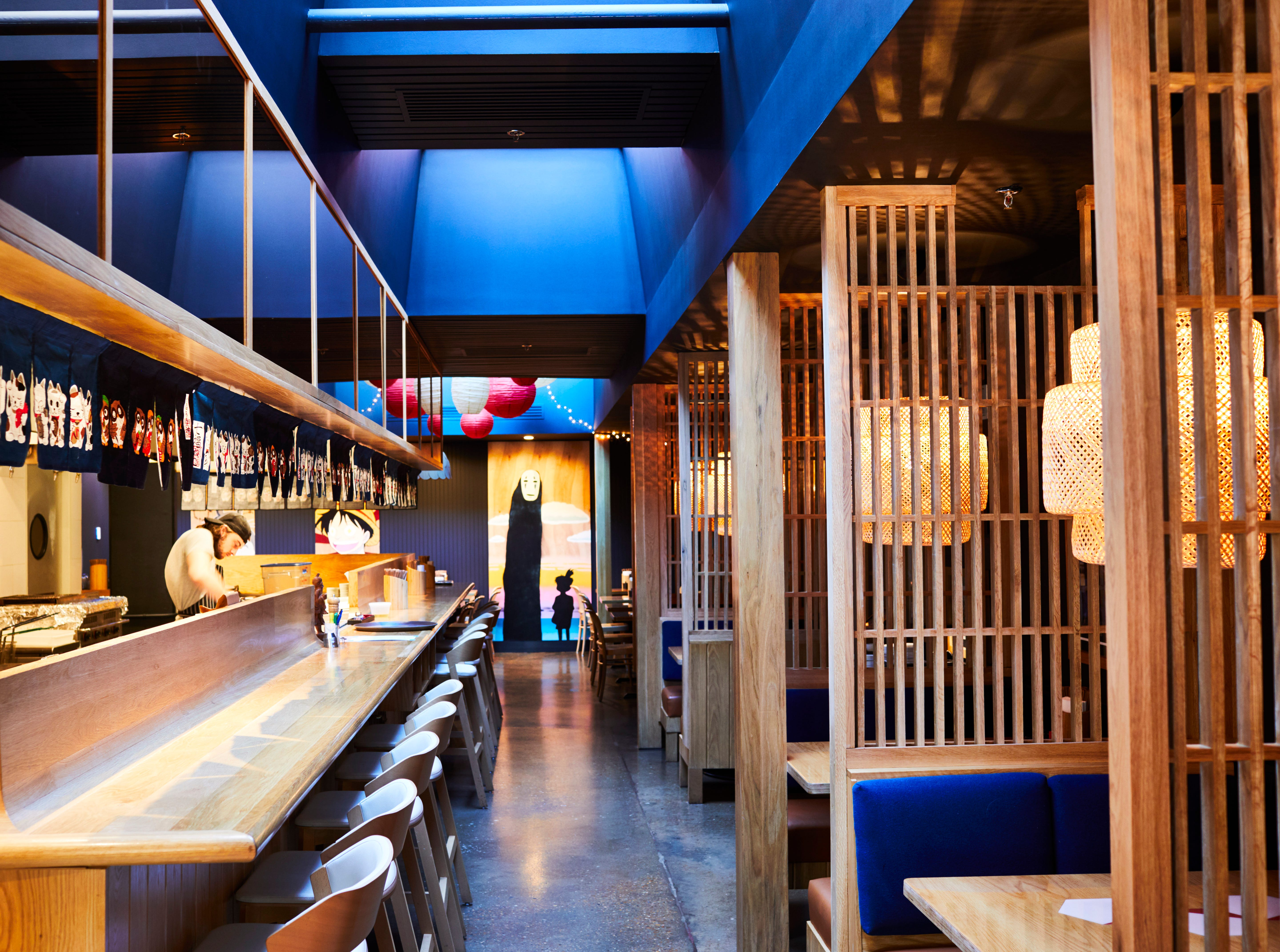 Booths and open kitchen counter seating at Bar Otaku.