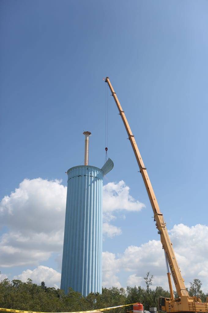 A crane prepares to winch down the final piece of a storage tank atop the unused Bonita Springs Utilities water tower on Tuesday.