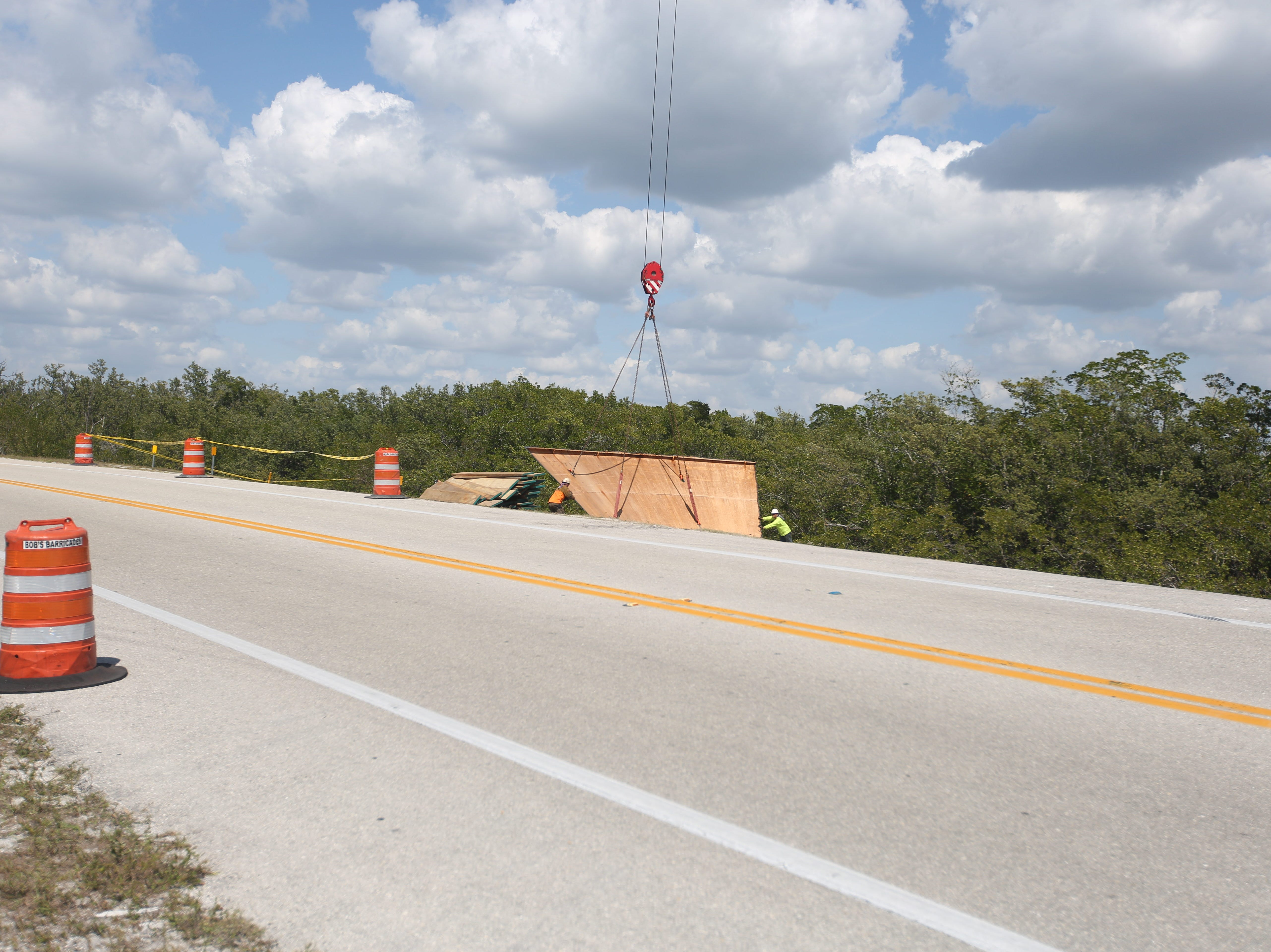 Workers finesse a piece of the water tower tank onto the ground on Big Hickory Island on Tuesday.