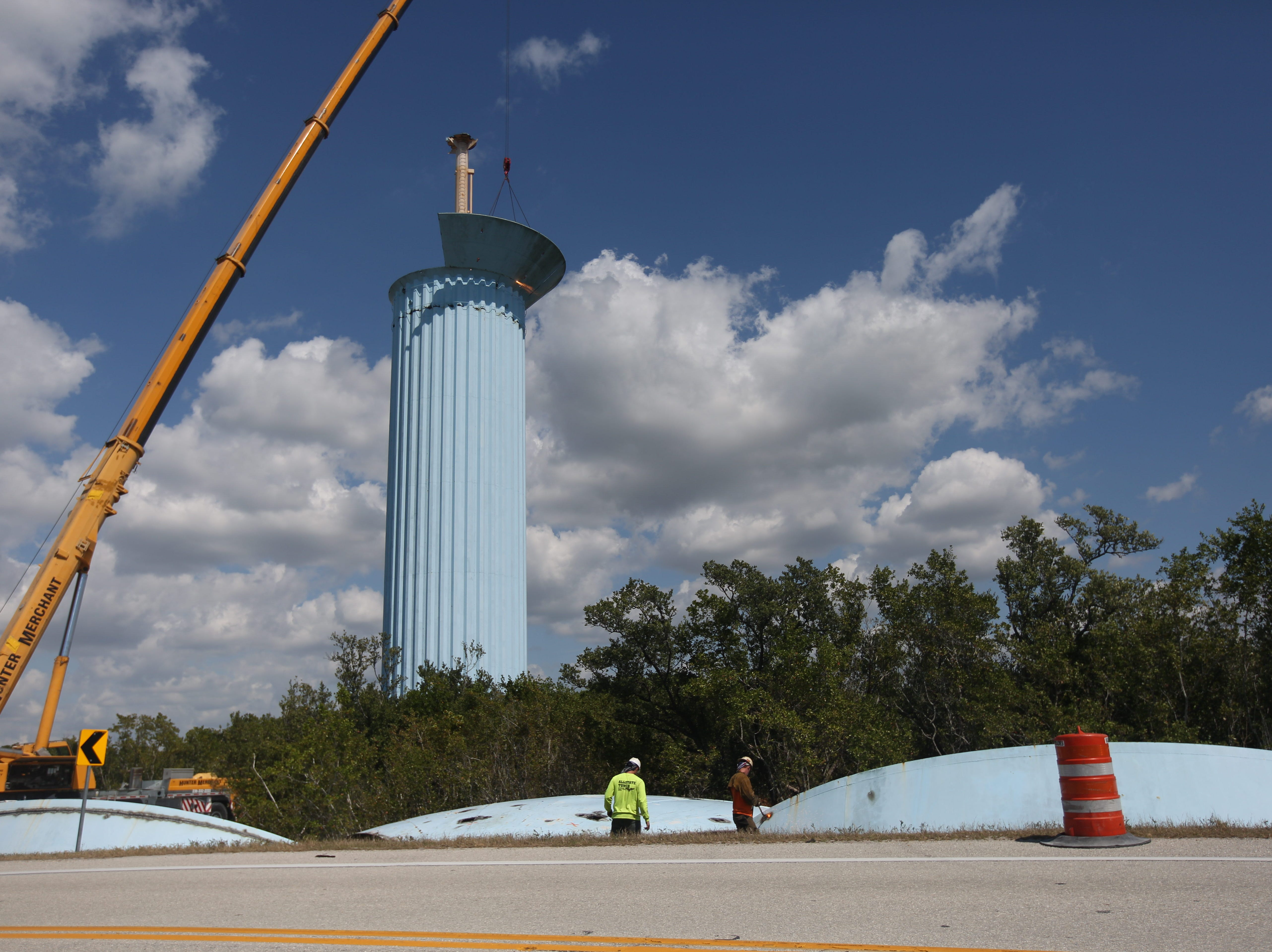 Workers begin cutting pieces of the dismantled Bonita Springs Utilities water tower on Big Hickory Island on Tuesday.