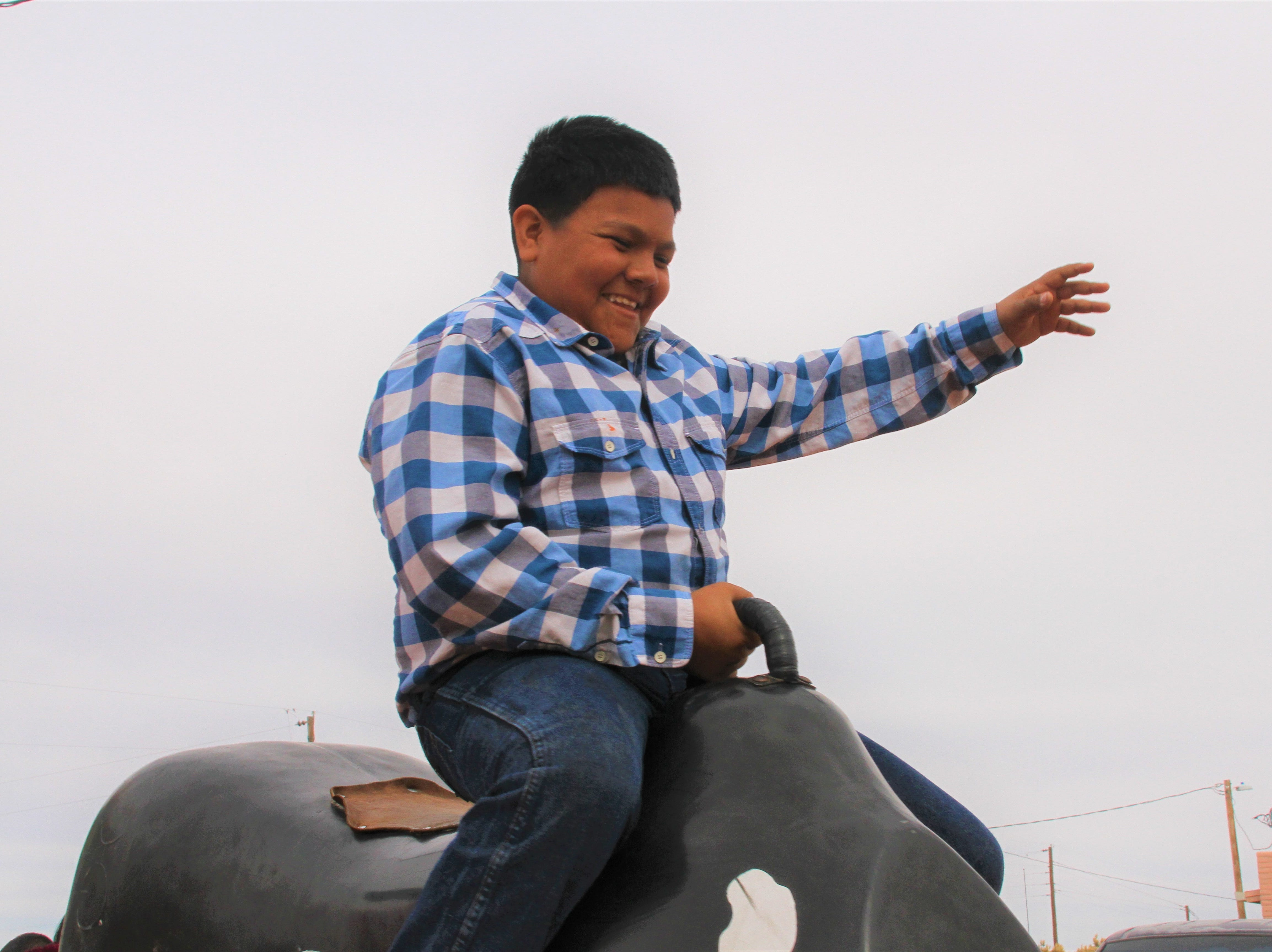 Ramon Quezada, 13, of Phoenix, Arizona riding a mechanical bull.