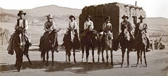 Some early cowboys pose for a camera shot.