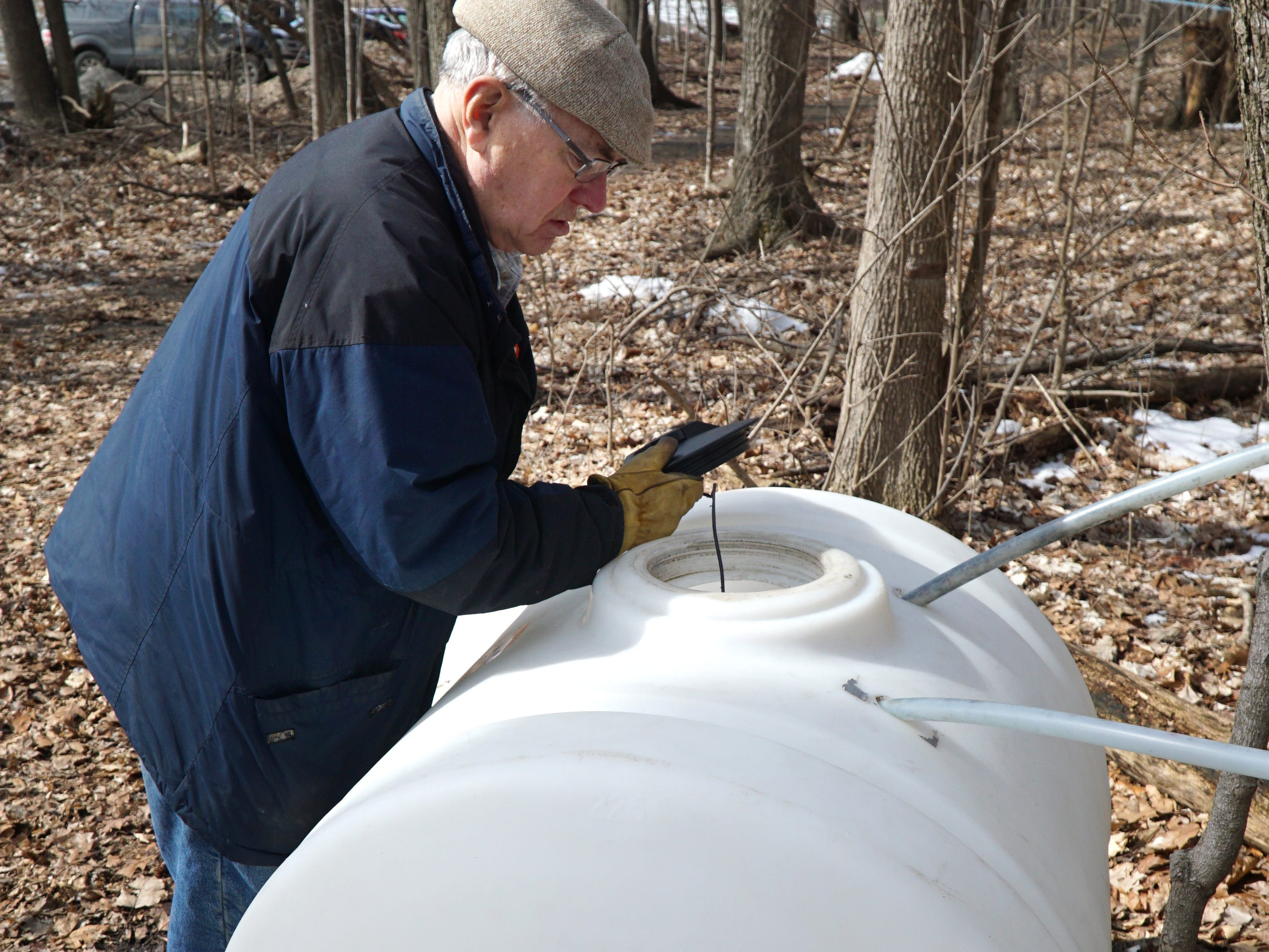 "John McInnis checks one of the storage tanks at Novi's Tollgate Farms' ""sugar bush"" area on March, 11. The sugar bush is where the farm has acres of maple trees that are tapped in later winter for their sap. McInnis has been part of the syrup production crew for more than two decades and began a Master Woodland Management Program at Tollgate to give students the experience of managing an active forest landscape. The sap in Tollgate's maple trees flows best when the nighttime temperatures are near freezing - but then warm during the day so that the sap can flow down to the taps."