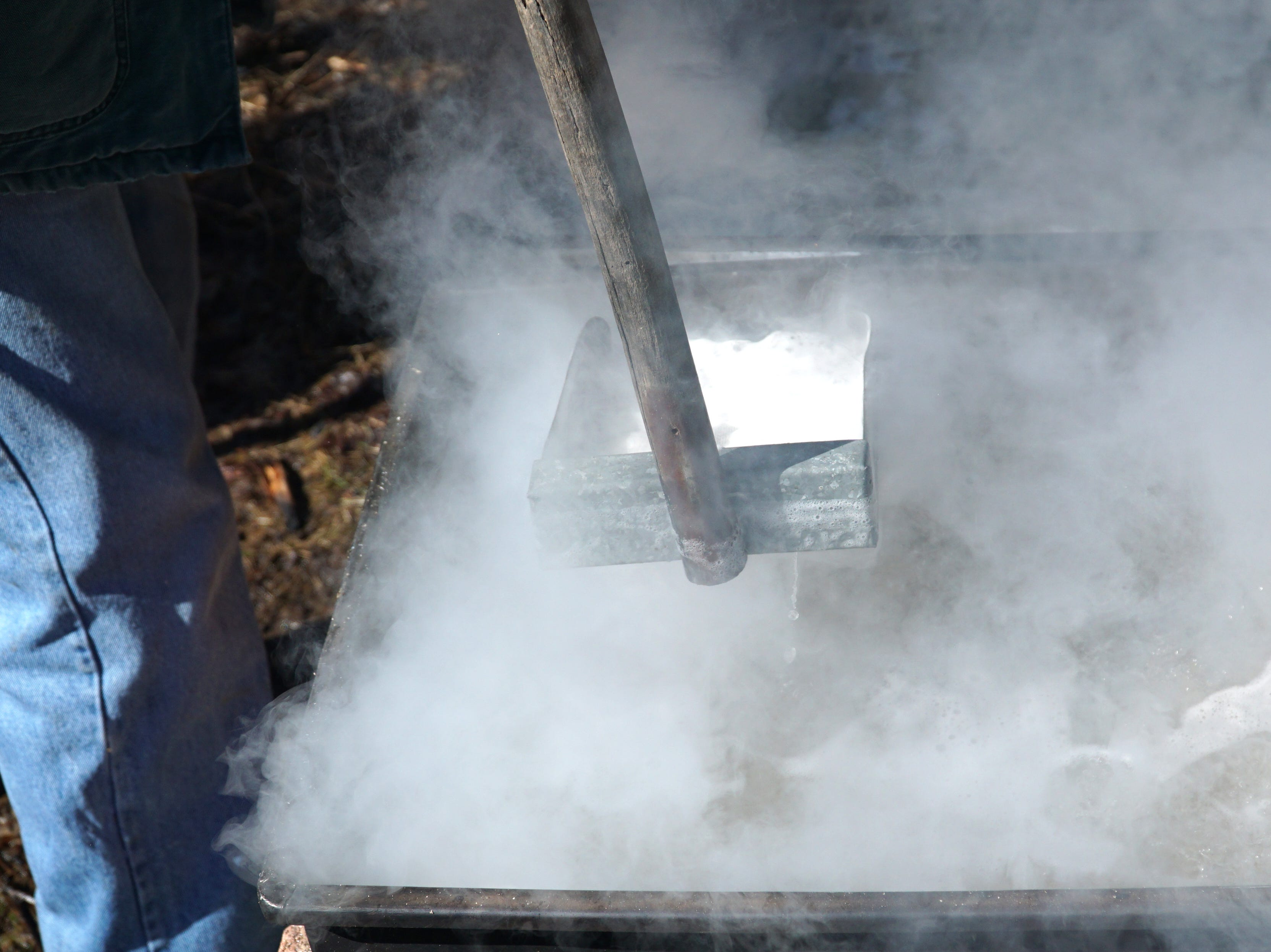 Larry Schmidt skims off scum from the boiling sap at the Schmidt property on March 12. If the scum is not taken off, the sap cannot boil off its water content.