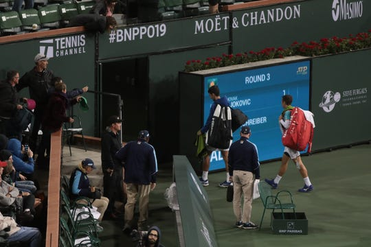 Novak Djokovic and Philipp Kohlschreiber walk off the stadium court due to a rain delay in their third round match at the BNP Paribas Open, Indian Wells, Calif., March 11, 2019.