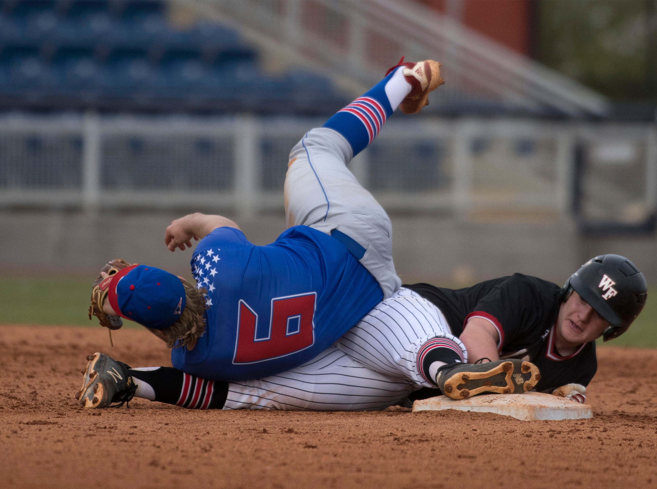 West Florida High School's Will Hackett,(No. 11) gets buried by Pace High School's Aidan Gilroy, (No. 6) after he fails to make a leaping catch during the Battle of the Bay tournament at Blue Wahoos stadium on Tuesday, March 12, 2019.