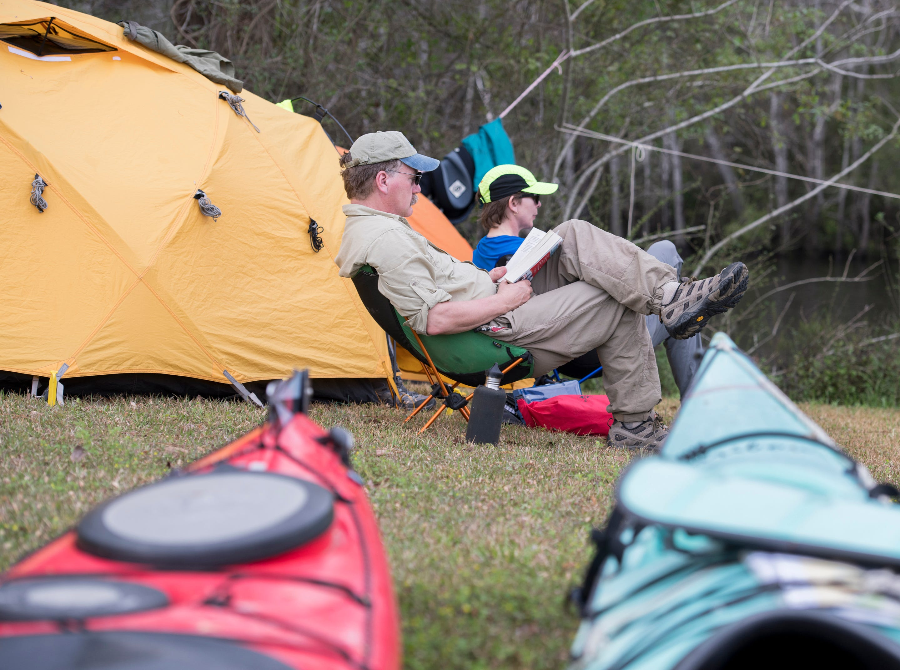 Greg Welker and Jenny Plummer-Welker, of Annapolis, Maryland, relax after setting up camp at the Wilson Robertson Boat Ramp on the Perdido River in Pensacola on Monday, March 11, 2019.  Paddle Florida is hosting 60 paddlers on a 5-day, 60-mile journey from Otto Hill to Perdido Pass.  Florida is currently working with Alabama to establish a paddling trail on the Perdido River.