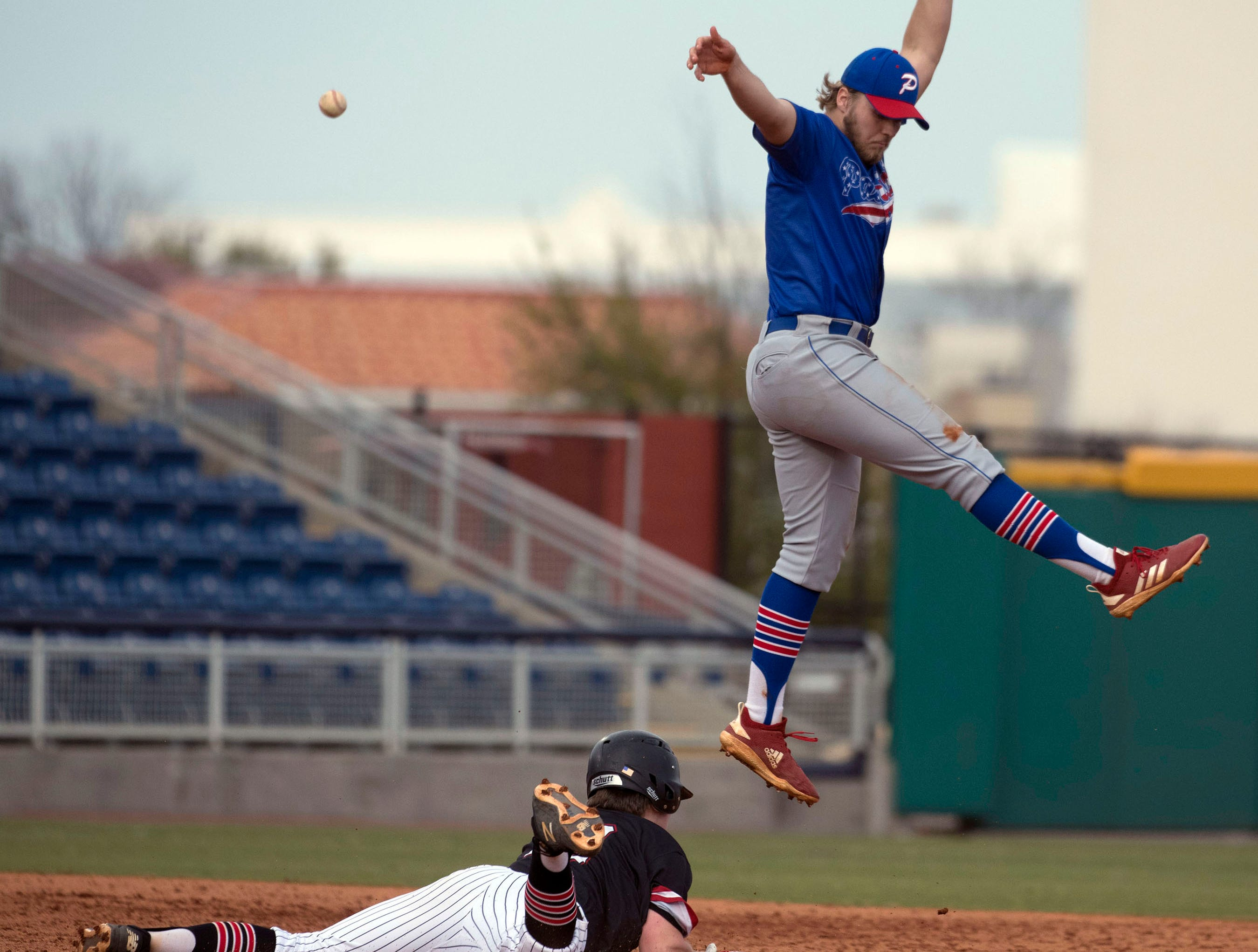 West Florida High School's Will Hackett,(No. 13) dives headfirst into second base as Pace High School's Aidan Gilroy, (No. 6) tries to make a leaping catch during the Battle of the Bay tournament at Blue Wahoos stadium on Tuesday, March 12, 2019.