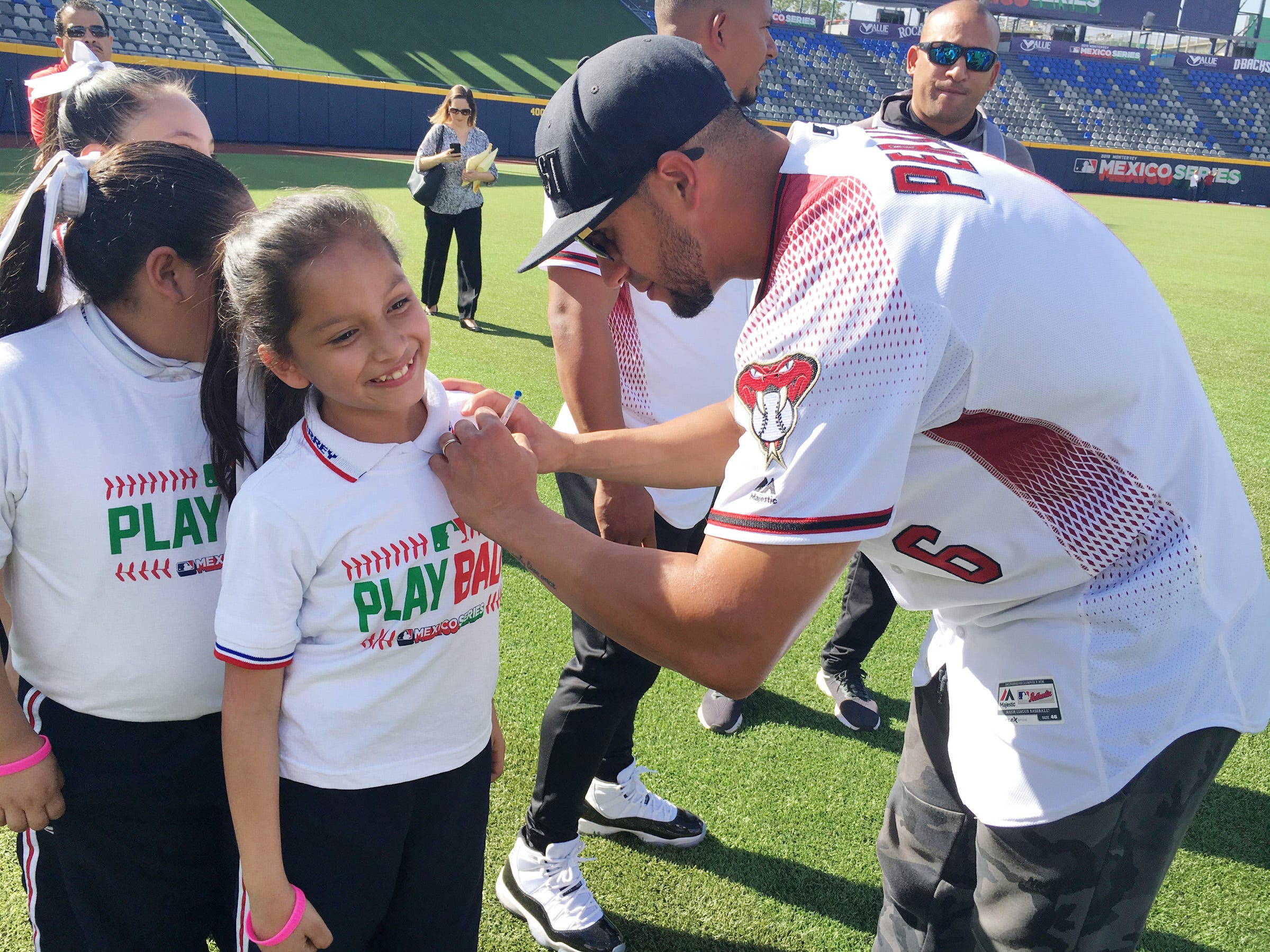 Arizona Diamondbacks outfielder David Peralta autographs the T-shirt of a girl inside the baseball stadium in Monterrey, Mexico. The Arizona Diamondbacks played two spring training games in Monterrey against the Colorado Rockies in March, as part of push by Major League Baseball to expand its global fan base.