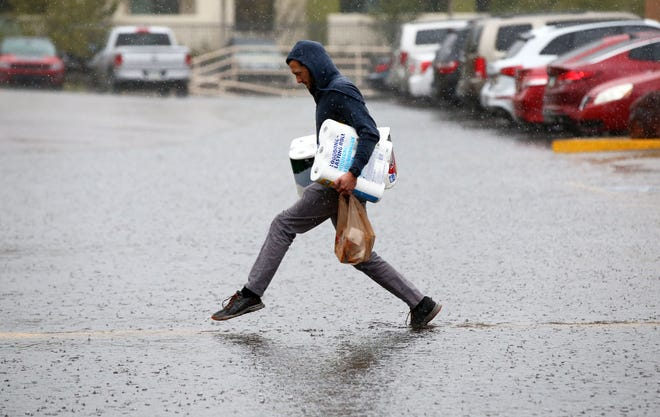 A shopper makes a run for his car near 32nd Street and Shea Boulevard during a rainstorm on March 12, 2019, in Phoenix.