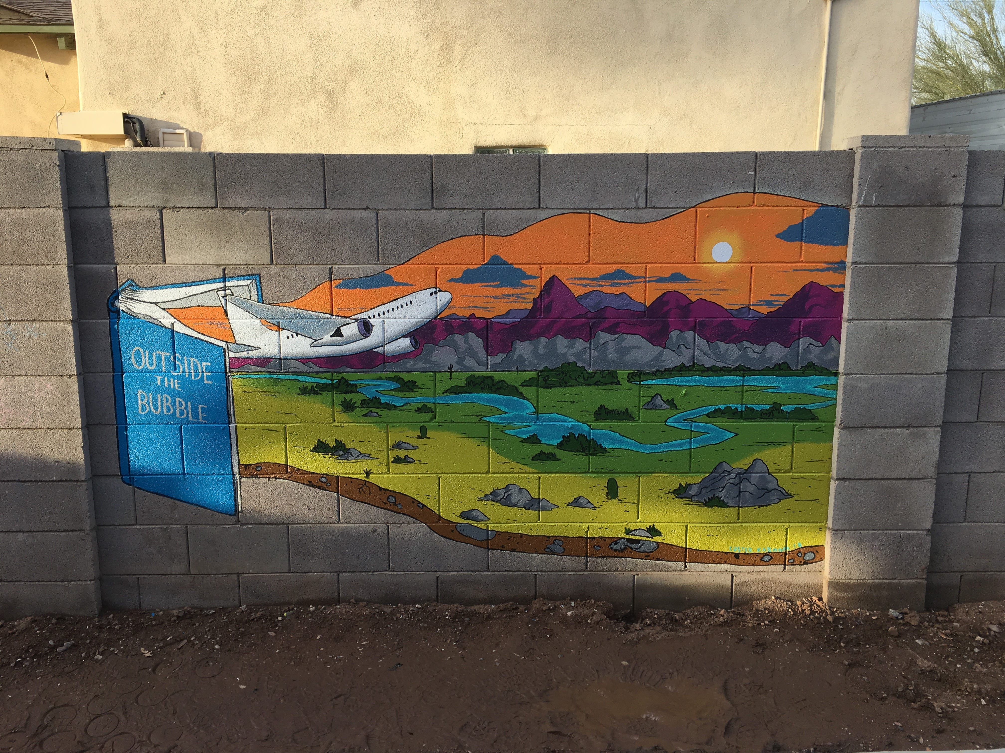 This mural was designed and painted by Luster Kaboom, a local artist, during the 2019 Coronado Historic Home Tour. The design reflects the owners' love of travel and reading.