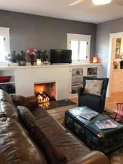 The original wood fireplace has been retrofitted with a gas unit to help reduce air pollution. A cracked marble façade was removed from the face of the fireplace, exposing fire brick.