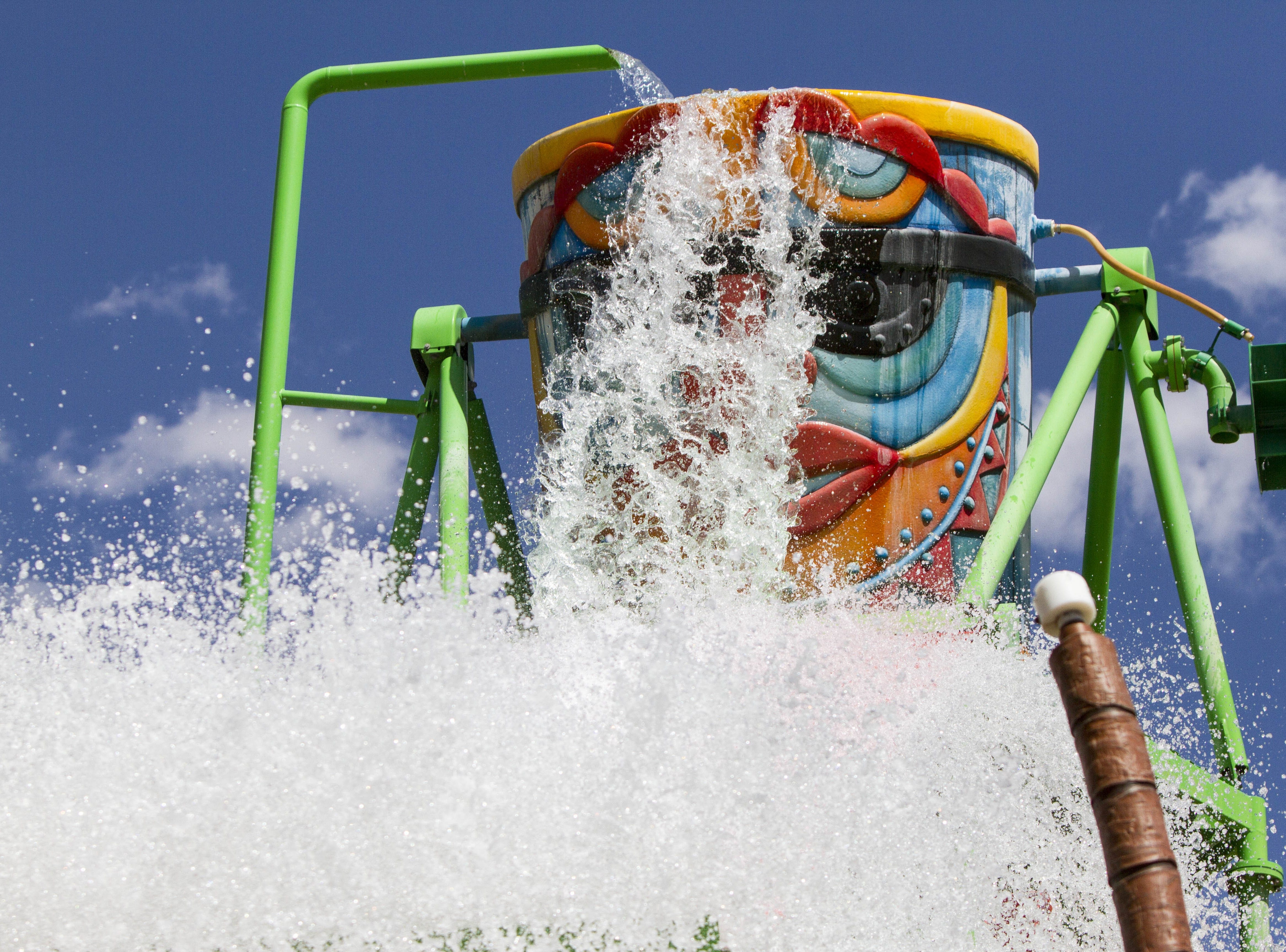 A giant bucket dumps water on people at Boogie Board Beach at Wet'n'Wild, Saturday, May 9, 2015, in Glendale, Ariz.